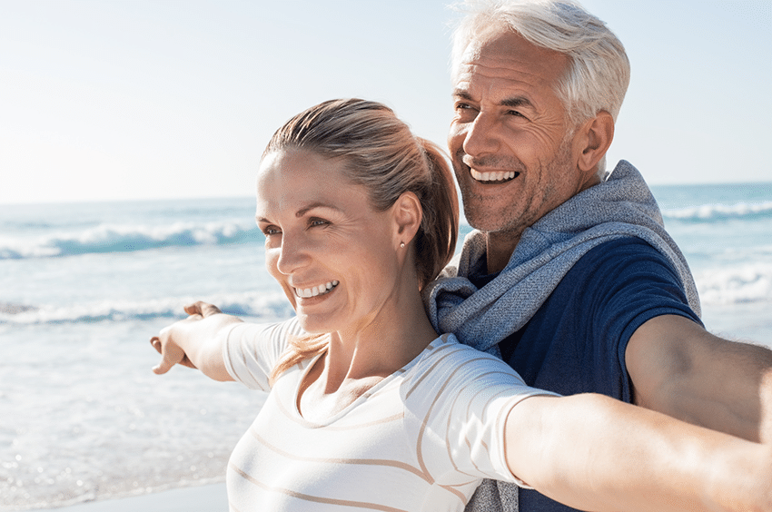 Man and woman smiling in front of the ocean on a beach
