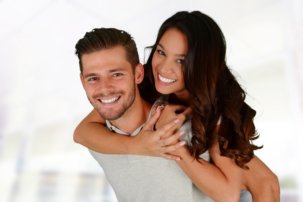 A young couple smiling because of the General Dentistry at Firouzian Dentistry in Columbus