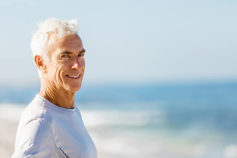 A elderly man smiling at the beach