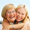 A younger woman hugging a older woman both smiling - Full Mouth Reconstruction