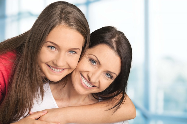Two young woman smiling and hugging