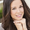 A young woman smiling with her hands under her chin - General Dentistry