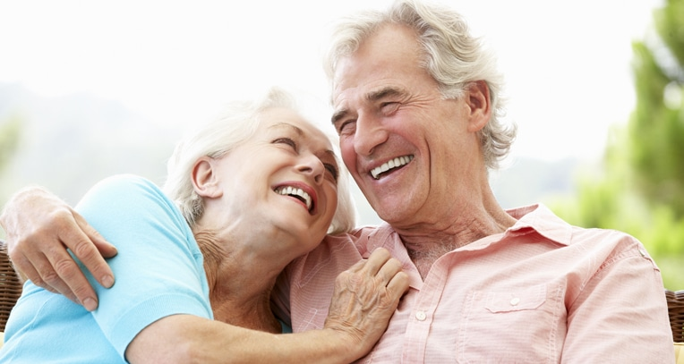A elderly couple smiling while looking at each other