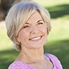A middle aged woman sitting outside smiling - Dentures Fountain of Youth