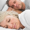 A middle aged couple sleeping soundly - Sleep Apnea