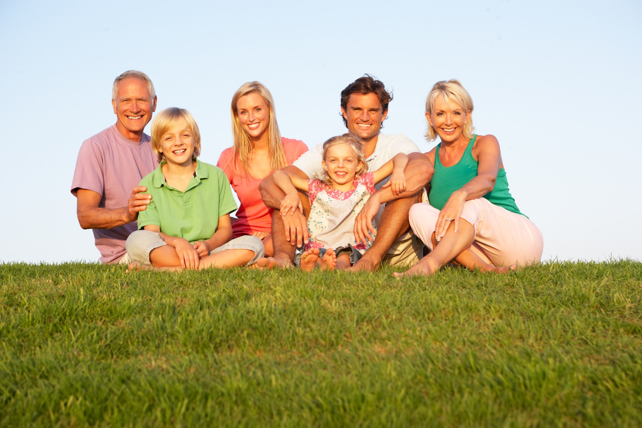 Photo of a happy family sitting in the grass, at a park.