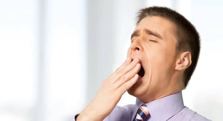 A middle aged man yawning because of his Sleep Apnea, for more information go to Firouzian Dentistry in Columbus