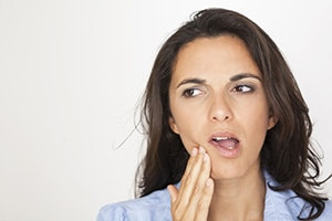 A woman with an open mouth and her hand rubbing her lower jaw in pain
