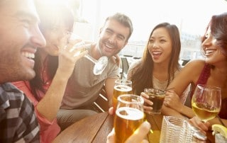 Five friends laughing and drinking together