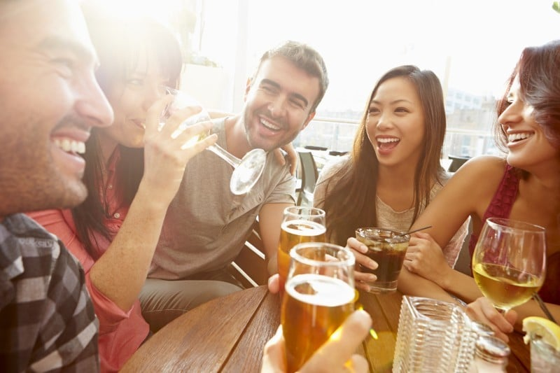 a group of young people smiling and drinking different drinks