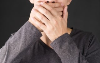 Close up of boy covering his mouth with both of his hands