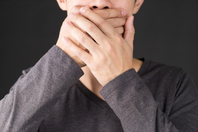 A man covering his mouth with both hands. His Partial Dentures are Causing Receding Gums - something that not only is embarrassing him but also causing him issue with his oral health.