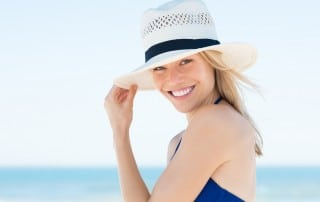 Woman in a sunhat smiling on the beach
