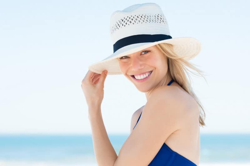 A young woman smiling wearing a sun hat at the beach