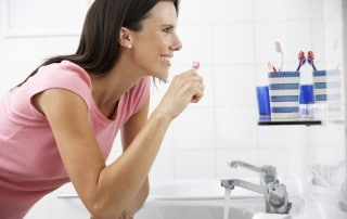 Woman smiling at her self in a mirror as she brings her toothbrush up to her mouth