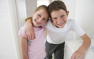 Young girl and boy smiling with arms around each other