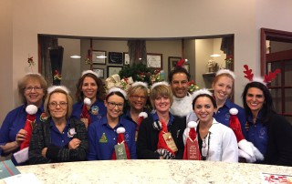 The Firouzian team wearing Christmas hats, mistletoe headbands, and reindeer headbands