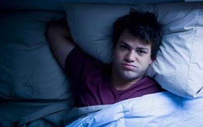 A young man lying awake in bed because of his Sleep Apnea