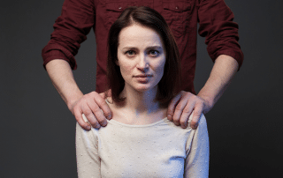 Woman sitting sadly while man's hands hold her shoulder's down