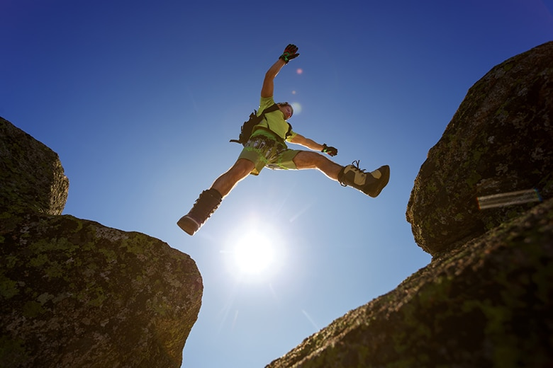 A photo of a person in mid air jumping a gap between two rocks.