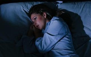 Woman lying awake in bed, unable to sleep