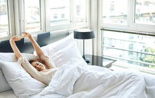 Young woman stretching while in bed waking up.