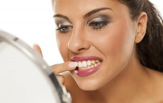 Woman looking in mirror while trying to get food out of her teeth