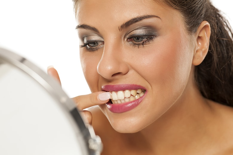 Attractive woman trying to remove food from in between her teeth