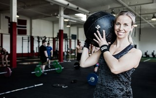 CEREC Crowns Stand Up to Fatigue like the Happy Young Woman Holding a Lifting Medicine Ball