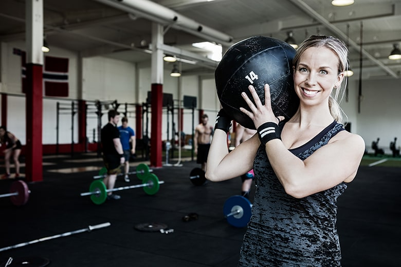 CEREC Crowns Stand Up to Fatigue like the Happy Young Woman Holding a Lifting Medicine Ball - even though she is fatigue she keeps coming back to the gym every day.