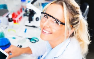Young attractive woman scientist writing research report in the laboratory. She's used science to improve her outlook