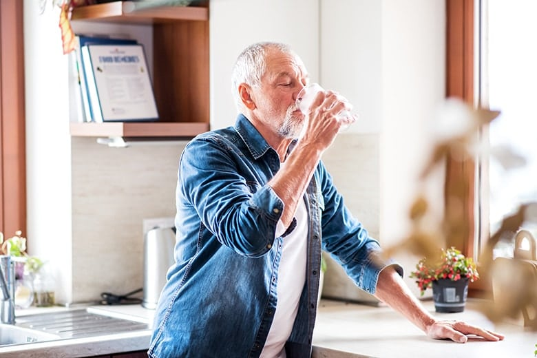 Senior man standing at the kitchen sink chugging water as he suffers from the autoimmune disease, Sjögren's Syndrome, commonly known as dry mouth. Even with this syndrome he is still a candidate for dental implants.