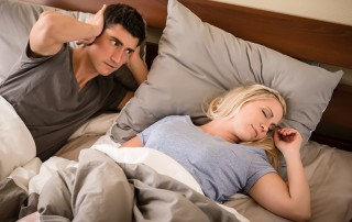 Young man annoyed by the snoring of his wife sleeping in bed at night. It common for women to not admit they snore but a study shows that 88% of women do.