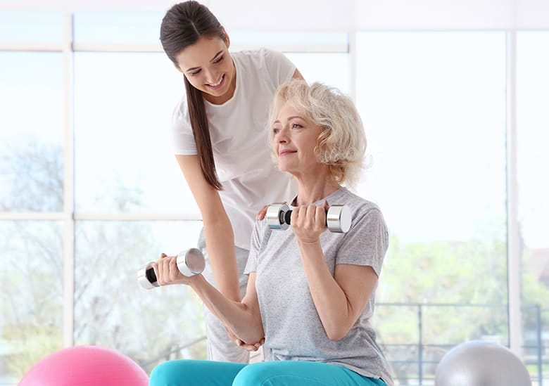Older woman working with a Physiotherapist in a clinic due to the woman's bone loss due to Osteoporosis. Do you suffer from tooth loss? Are you looking for a better way than dentures to replace your missing teeth? Dental implants are a great option.
