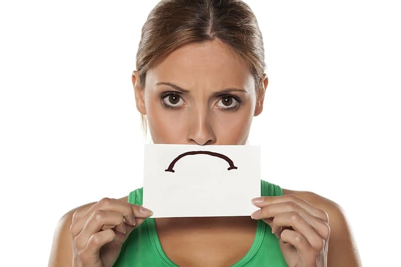 A young woman with a paper frown sad face hiding her real smile. If you are considering straightening your teeth, think twice before seeking an option just because it's cheap like Smile Direct.