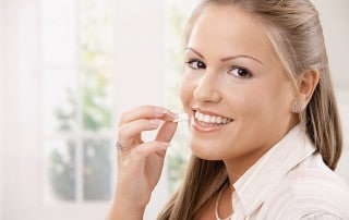Beautiful woman placing a piece of gum in her mouth. Although chewing gum can often be perceived as a dirty or annoying habit, it may actually help prevent cavities.