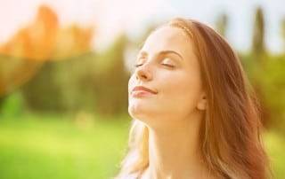A beautiful woman standing outside getting fresh air. Just like the air she's breathing in, it's important to have fresh breath when you are talking to others.