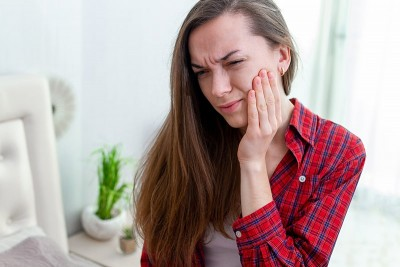 woman with jaw pain holds her face while suffering