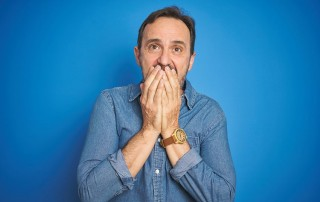Middle aged man embarrassed by his dentures covers his mouth with his hands