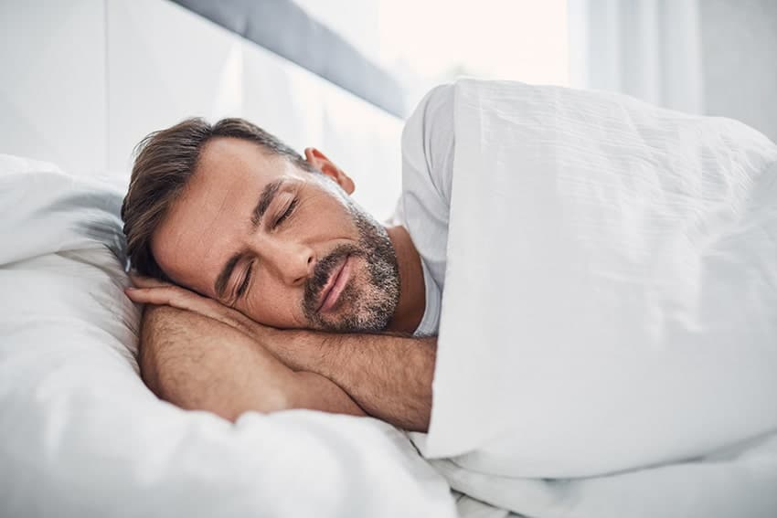 man rests peacefully in bed