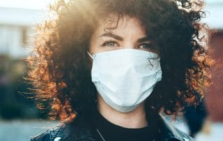 curly haired woman wearing a face mask