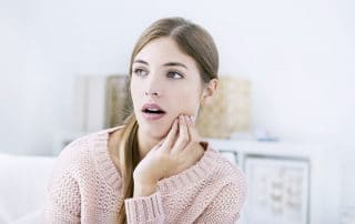 young woman sitting on her bed with jaw pain