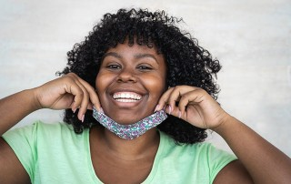 woman revealing her smile from under a mask